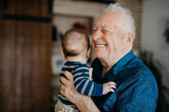 Elderly man smiling carrying a baby