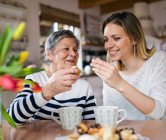 elderly woman having coffee with younger woman.